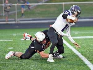 Delano's Spencer Poll takes down Little Falls quarterback Austin Udy for a sack in the first quarter last Friday night. The Tiger defense allowed the Flyers to cross midfield just three times in the game. Photo by Matt Kane