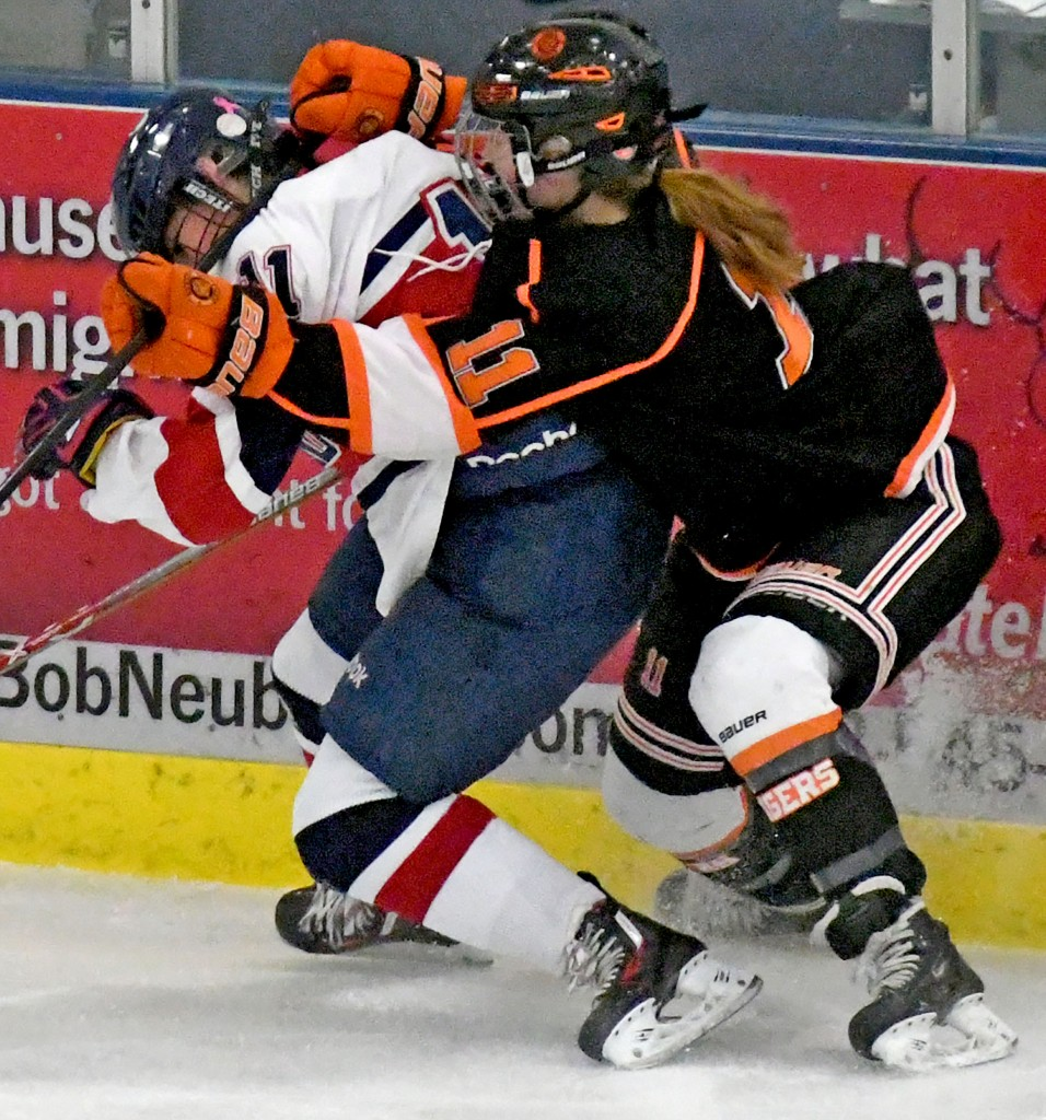 The rivalry brought out some physical play Friday night, when Orono hosted Delano in a WCC game. Here, Delano's Emily Olson gives Megan Marzolf a greeting in the first period. The visiting Tigers dished out the final blow, winning the game 2-1 in overtime. Photo by Matt Kane
