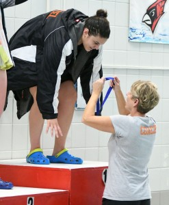 Delano senior Jordyn Wentzel receives her first-place medal for her Section 3A win in the 500 freestyle from head coach Karen Shallbetter last Saturday at Willmar High School. Wentzel's record time of 4:59.86 ranks first heading into Friday's state preliminary round. She also won the 100 breaststroke at the section meet. Photo by Matt Kane