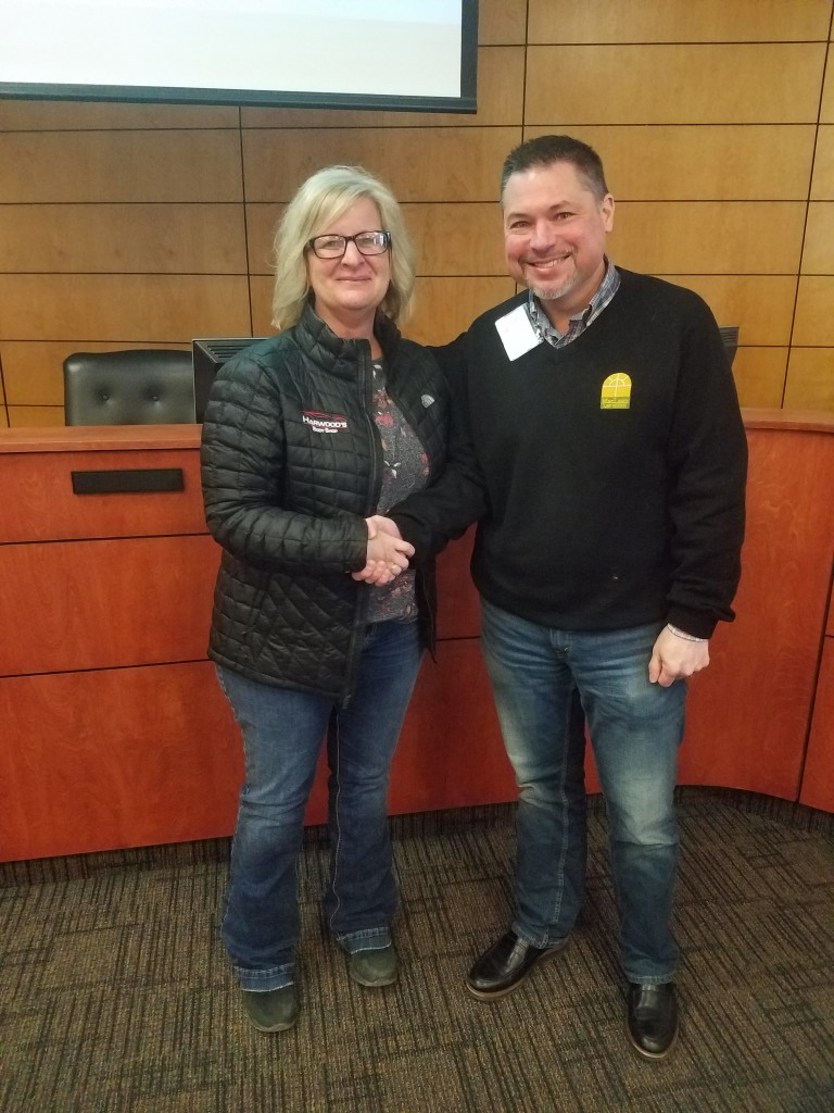 Delano Area Chamber of Commerce Treasurer Daryl MacLean congratulates Michelle Harwood, of Harwood's Body Shop, which was announced as the DACC's Business of the Year Thursday. See more information in the Friday, Feb. 21, edition of the Delano Herald Journal.