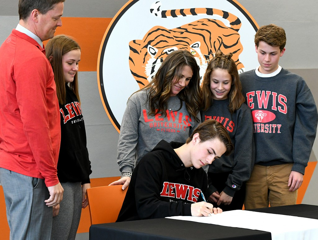 Sam Kern signs a letter of intent to play lacrosse at Lewis Univeristy Wednesday at Delano High School. Looking on are dad Phil, sister Emma, mom Melanie, sister Bella and brother Colby. Kern will first finish his senior season at Delano. Photo by Paul Downer