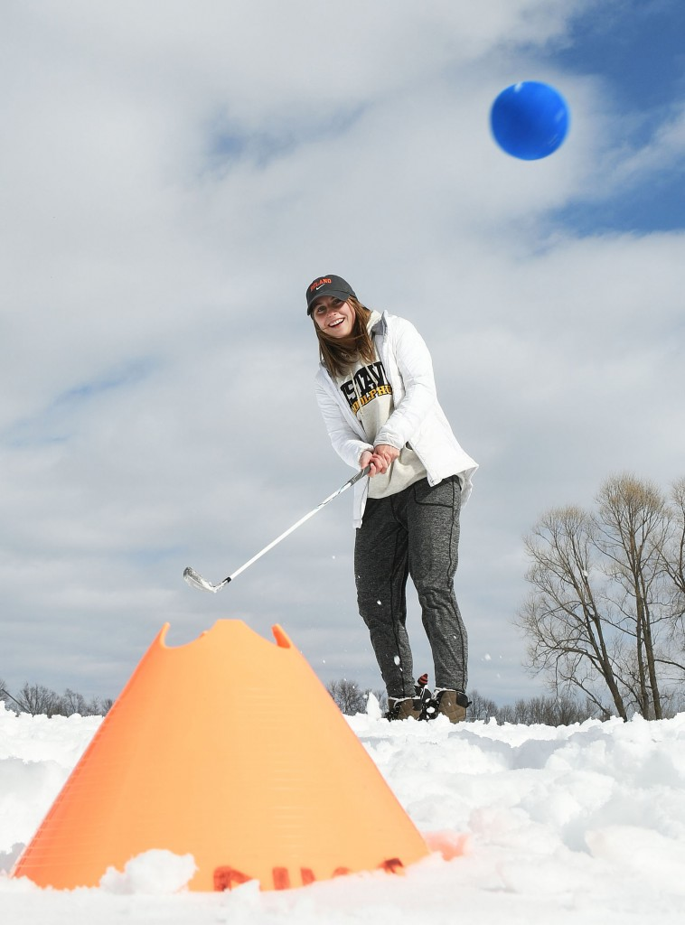 SNOW BIRDIES Tired of golfing in the wrestling room, the Delano girls took some shovels and clubs outside Monday for nine holes in the deep snow behind the Delano Area Sports Arena. The bright sunshine and this chip shot put a smile on the face of senior Jamie Byrne. Photos by Matt Kane