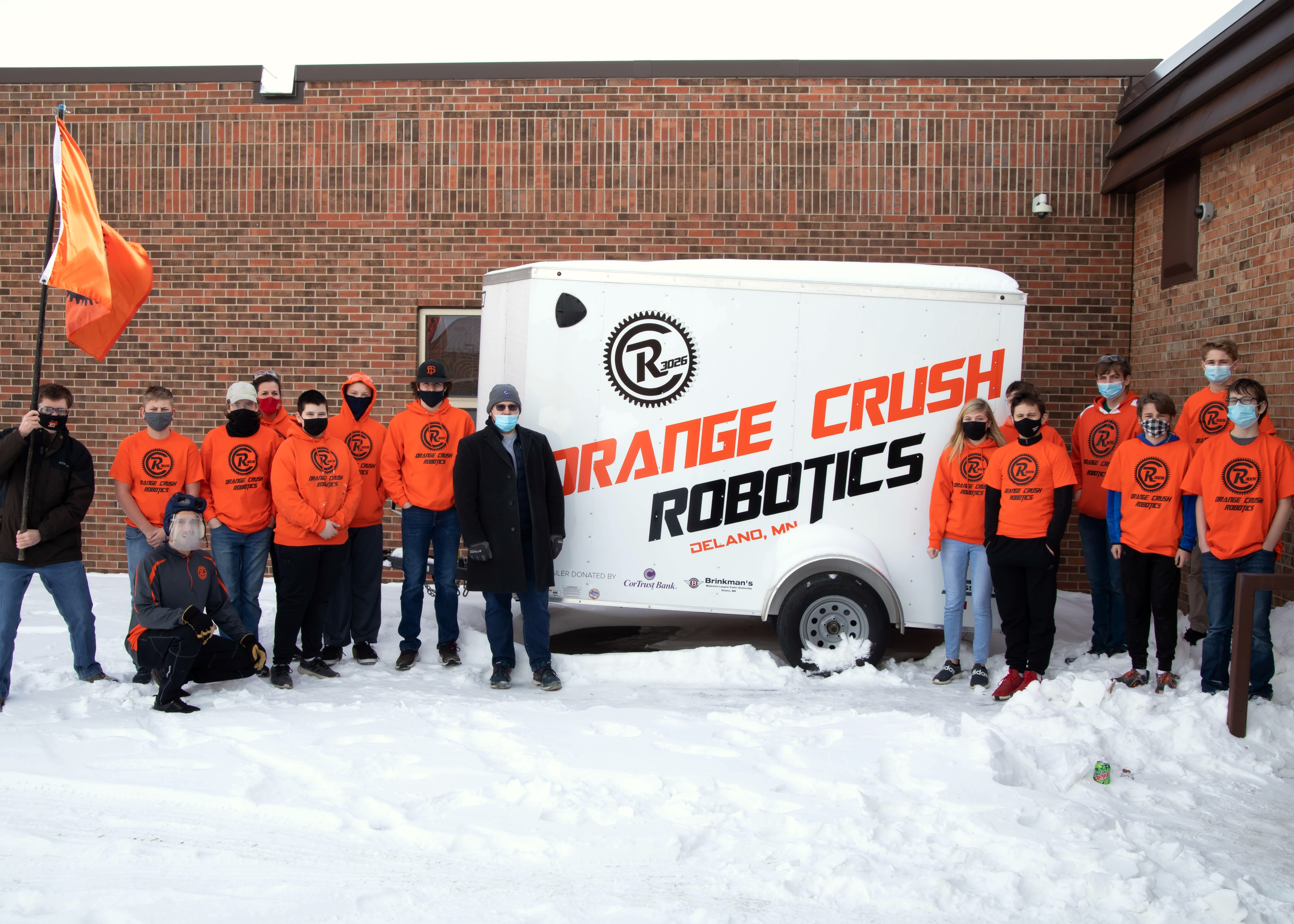 The Orange Crush Robotics team is pictured with a representative of CorTrust Bank, which donated the trailer.