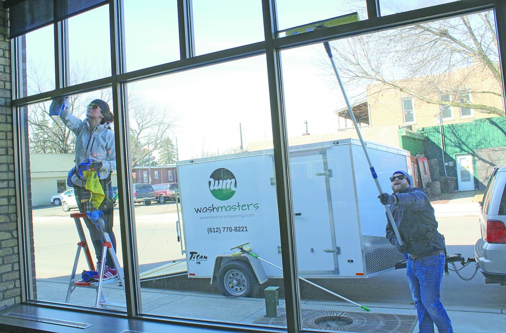 Ashley and Mike Maharas, of washmasters, wash windows at Bonde Bistro on a brisk March morning.  The Delano couple began washing windows together full-time in early March.